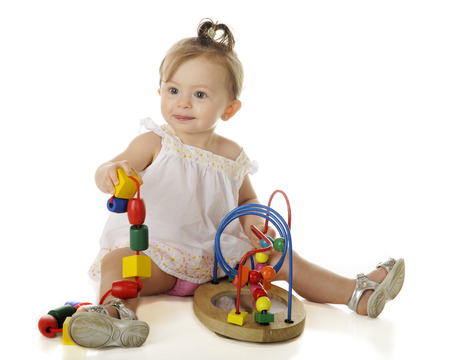 An adorable baby girl playing with large, colorful beads, some on a string, others on a wire frame.  On a white background.