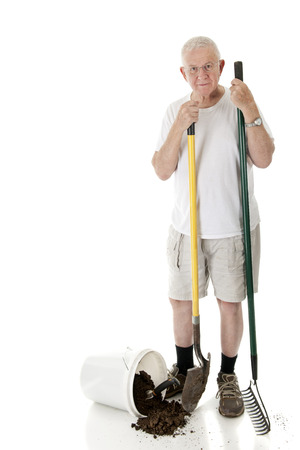 A senior man looking at the viewer as he holds a garden rake and shovel, a bucket of spilled dirt at his feet.  On a white background with space on his right for your text. Stock Photo