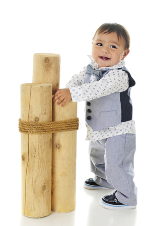 An adaorable, dressed up baby boy holding on 3 mooring posts as he steadies himself for standing.  On a white background.