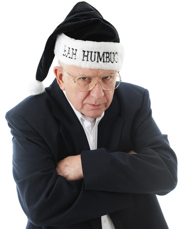 Close-up image of a grumpy old man in black, wearing a black Bah Humbug Sanata hat.  On a white background.