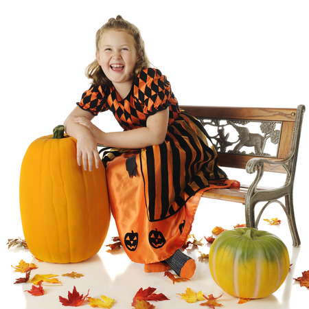 An elementary girl in a shiny orange and black dress laughing as she leans on a tall pumpkin.  She's sitting on a park bench and surrounded by colorful fall leaves.  On a white background. photo