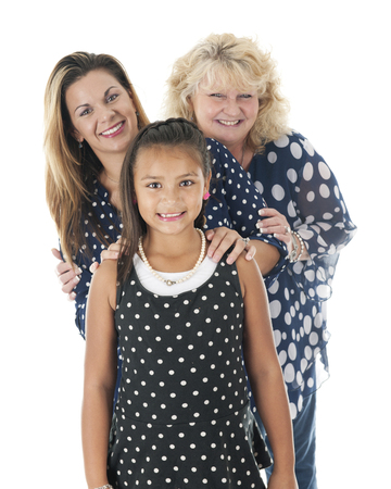 three generations: Three generations of women happily standing together in their navy and white polka dot tops.  On a white background. Stock Photo
