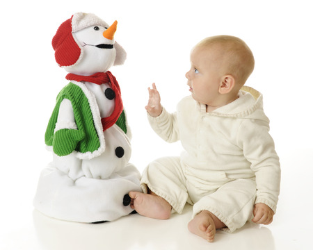 An adorable baby boy looking up skeptically at a toy Christmas snowman, wondering if he is touchable.  On a white background. photo