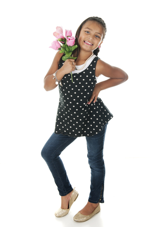 sassy: A pretty elementary girl looking sassy as she stands with a bouquet of pink roses.  On a white background.
