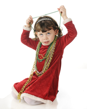 velvet dress: An adorable dressed up preschooler looking up as she removed strands of Christmas beads from around her neck.  On a white background. Stock Photo