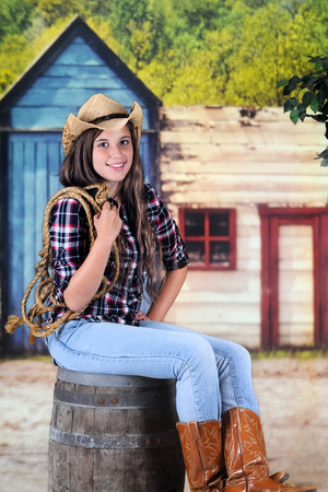 wildwest: A beautiful young teenage cowgir holding a rope while sitting on an old barel in a wild-west town. Stock Photo