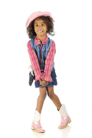 An elementary African American standing in her cowgirl outfit in an awkward position -- knees together, toes apart.  Isolated on white.