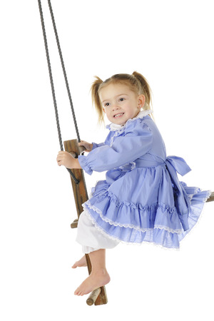 An adorable preschooler in an old-timey dress and bloomers happily swinging on an antique wooden pump swing.  On a white background.