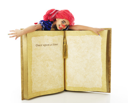 rag doll: A young elementary rag doll flopped across a giant book, opened to the words Once upon a time.  The rest of the page is left blank for your text.  On a white background. Stock Photo