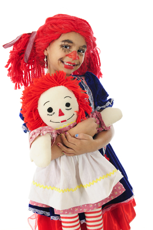 An adorable little girl rag doll happily holding her toy rag doll.  On a white background.