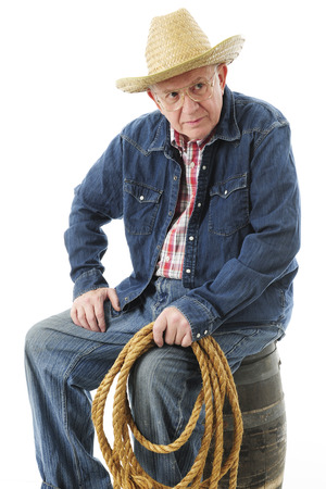 A senior adult cowboy appearing skeptical while sitting on an old barrel.  On a white background. photo
