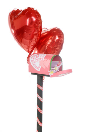 A Valentine-decorated mailbox flanked with two hearshaped balloons.  revealing mail. The mailbox is opened, revealing flowers and envelopes. Stock Photo