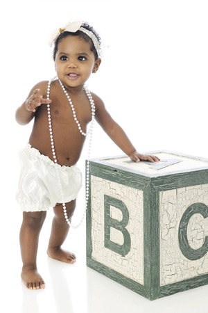 A beautiful baby girl standing with the help of a giant alphabet block.  Shes wearing a white hair bow, strans of beads and a silky diaper cover.  On a white background.