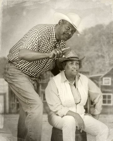 A senior African American couple together in an old wetern town.  Hes leaning over her, pointing towards something.  Shes sitting on a barrel trying to see what hes talking about.  Sepia toned and antiqued.