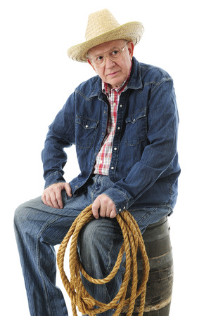 A senior adult cowboy resting on an old barrel with a rope in his hand.  On a white background. photo