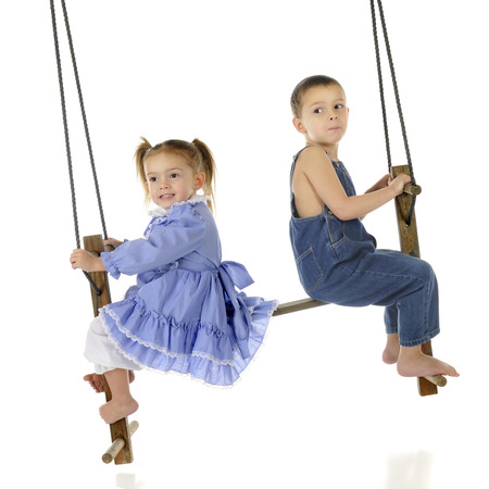 A preschool brother and sister swinging together on a rustic, antique 2-person swing.  On a white background. photo