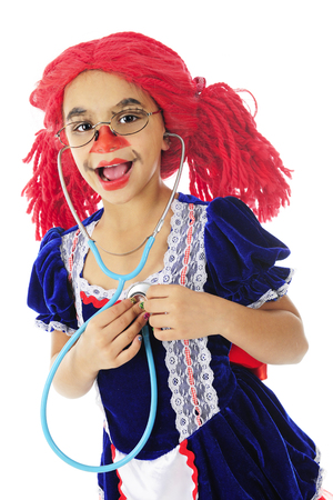 An adorable elementary rag doll deslighted as she listens to her own heart with a stethoscope.  On a white background.