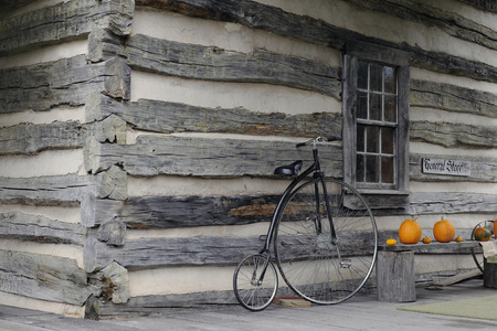window bench: Simple exterior of an old-time general store.  A bicycle leans near a window, with pumpkins on a bench nearby.