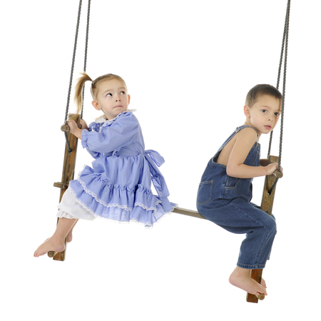 A preschool boy and his younger sister swinging on an antique, wooden, two-person pump swing.  The girl is looking over her shoulder at the top of the swing while the boy looks a bit worried at the viewer.  On a white background. Stock Photo