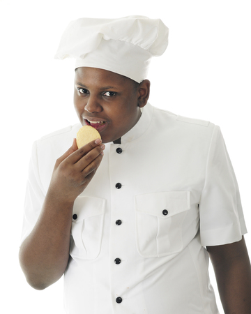 A young African American chef taste testing his sugar cookie.  On a white background.