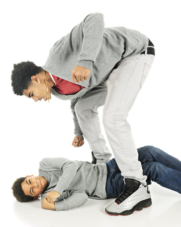Two brothers fighting.  A tall older teen stands over his elementary brother who is cringing while nearly flat on his back.  On a white background. Imagens