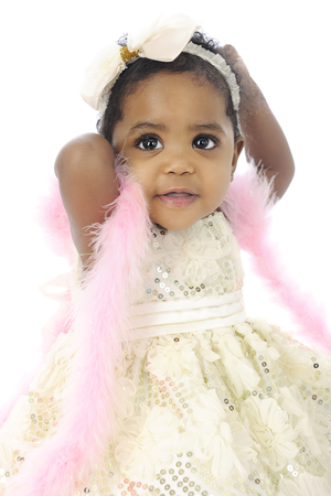 dressy: Portrait of a beautiful baby girl all dressed up in a white hair bow, sequin dress and pink boa.  On a white background.