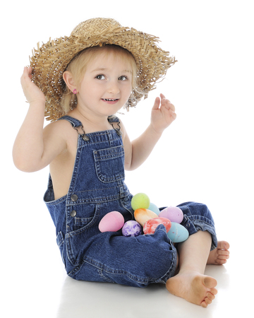 An adorable preschool farm girl sitting cross-legged in her ragged straw hat and denim overalls with a lap full of colorful eggs.  On a white background. Stock Photo