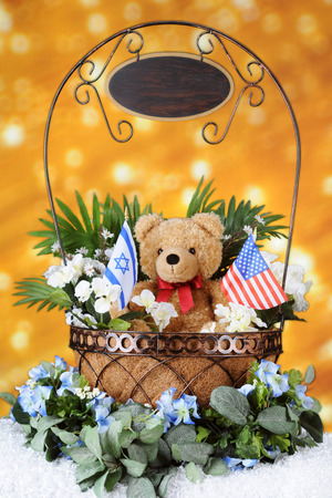 A wire basket filled with foliage and a tan teddy bear holding an Israeli and American flag -- all before a bank of golden lights.  A sign dangles from the handle.  It's left blank for your text.