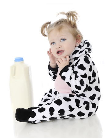 An adorable baby gilr wondering what she's doing in a cow outfit sitting by a half gallon of milk.  On a white background.