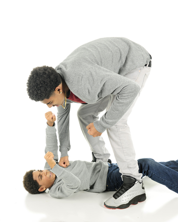 Fighting brothers.  A tall older teen punching his elementary brother who is flat on his back but punching back.  On a white background. Stock Photo