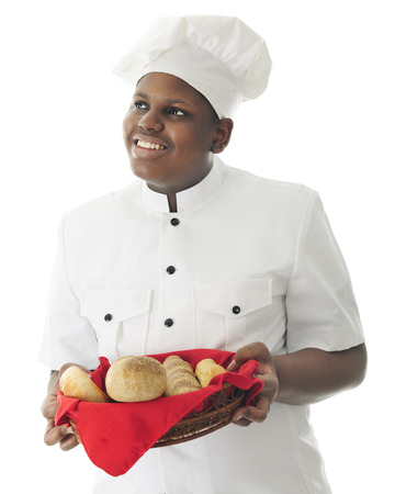 A young African American chef looking up as he carries a basket with a variety of breads.  On a white background. Imagens