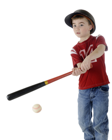 A young elementary boy batting a baseball.  On a white background.