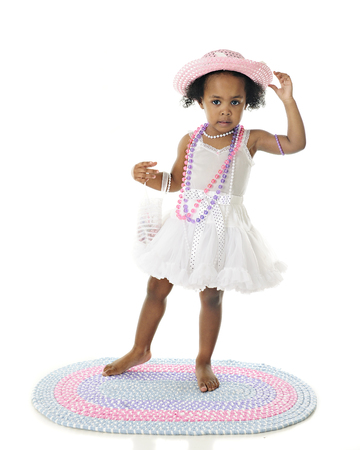 An adorable barefoot two year old dressing up in her petticoat, and pastel pearls, purse and hat.  On a white background.
