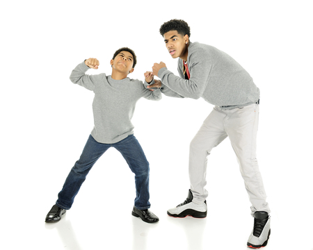 A elementary boy ready to take a punch at his tall big brother.  On a white background. Stock Photo
