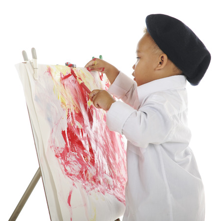Profile of an adorable preschool artist wearing a French beret and white smock, putting the finishing touches on his water color painting.  On a white background. photo
