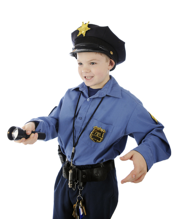 A happy elementary boy shining his flashlight while in his police uniform.  Isolated on white.
