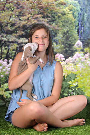 A pretty, barefoot teen girl happily squinting as her new puppy gives her a kiss on a beautiful summer day.