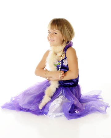 A dressed up elementary girl looking sheepish as she gets her hands stuck in the bangles she wears on each arm.  On a white background.