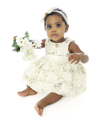 Full-length image of a beautiful baby girl, all dressed up in white holding a bouquet of white flowers.  On a white background.