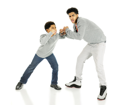 An elementary and tall, older teen boy looking at the viewer who has caught them fighting.  On a white background.