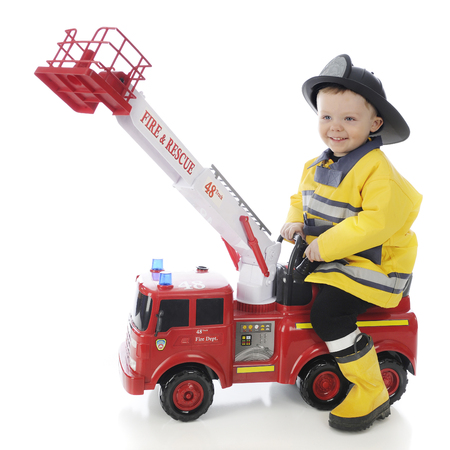An adorable toddler boy happily riding a toy firetruck in his fireman's outfit.  On a white background. Imagens