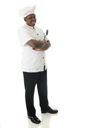 Full-length image of a young chef standing proudly with his arms folded and his spatula in hand.  On a white background.