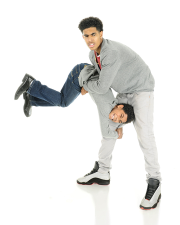Two brothers wresting.  The older teen has picked up the middle of his elementary aged brother who is clinging upside down to one of tall boys his legs.  On a white background.