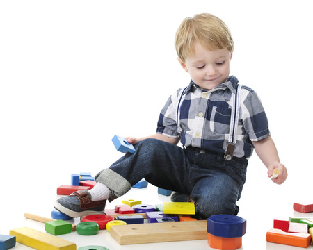 An adorable toddler playing with colorful blocks and stack toy.  On a white background with plenty of space on the left for your text.