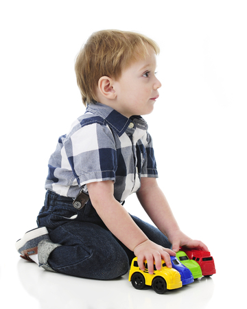 Profile of an adorable 2-year-old looking after he's lined up his toy vehicles.  On a white background.