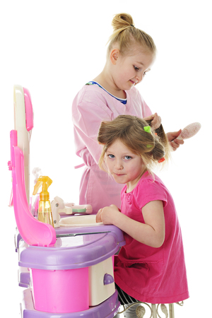 Two little girls playing beauty salon, the older girl brushing out her sister's hair. Focus on sitting child.  On a white background.