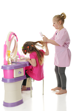 Two sisters playing Beauty Salon. The younger one tries to stop the older one from hurting as her hair is brushed. On a white background.