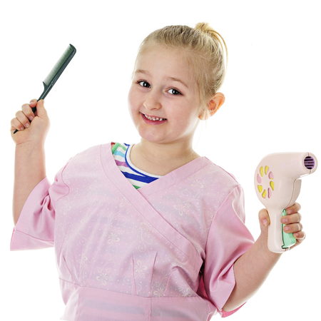 Close-up of a young elementary girl happily playing hair stylist.  On a white background. Imagens