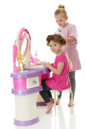 Two sisters playing beauty parlor. Focus on younger girl with curlers in her hair. On a white background.