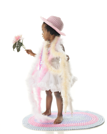 boas: Full-lenght profile of a 2 year old diva.  She stands barefoot in her petticoat and is wrapped in pastel beads and boas.  On a white background. Stock Photo